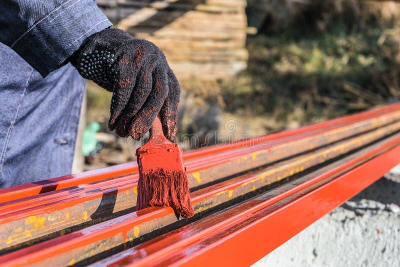 De schilder schildert metaalstructuren Beschermende deklaag van staal gesloten profielen met het rood van het inleidingsijzeroxid royalty-vrije stock afbeelding
