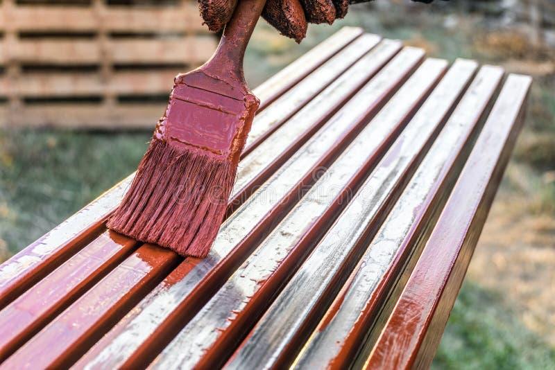 De schilder schildert metaalstructuren Beschermende deklaag van staal gesloten profielen met het rood van het inleidingsijzeroxid royalty-vrije stock fotografie