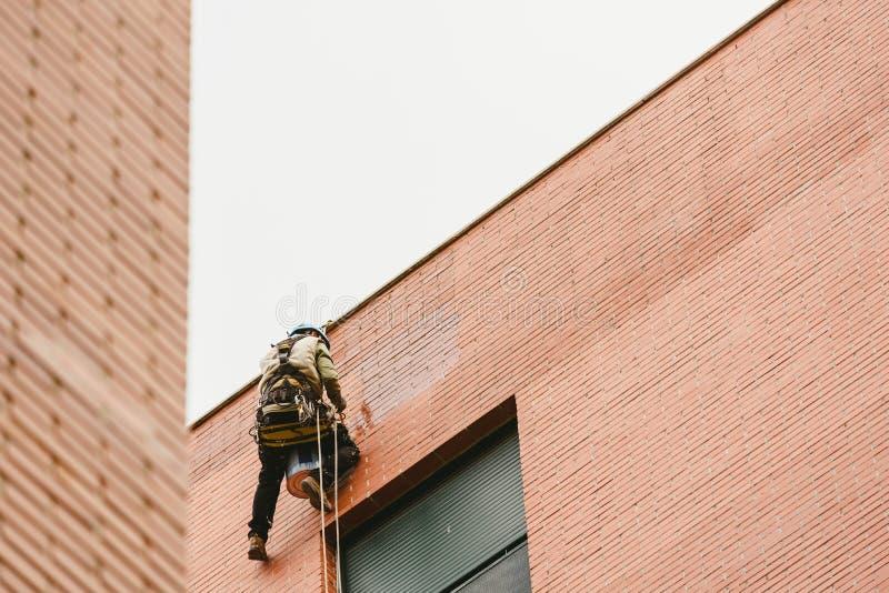 De schilder van de klimmer die van kabels wordt opgeschort en de harnasschilderingen schilderen de buitenkant van een appartement royalty-vrije stock afbeelding