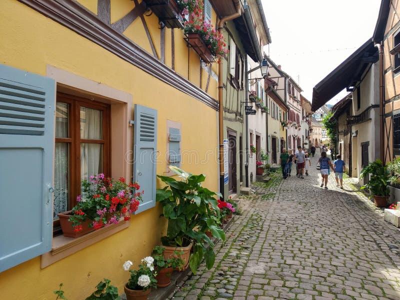 De schilderachtige stegen van Eguisheim, tipical oude huizen in Rijnstijl, verfraaiden met bloemen frankrijk stock fotografie