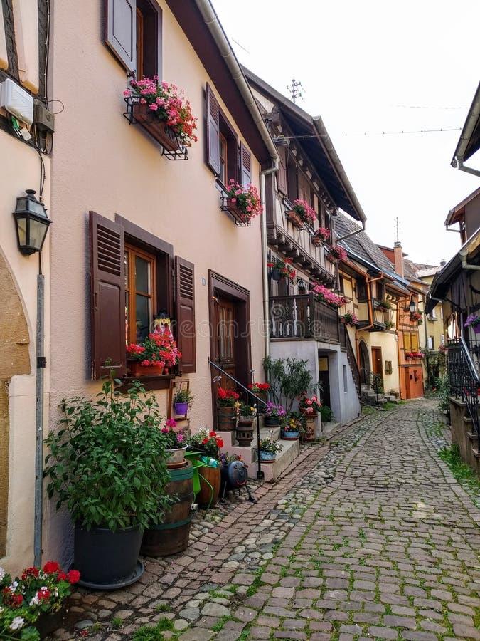 De schilderachtige stegen van Eguisheim, tipical oude huizen in Rijnstijl, verfraaiden met bloemen frankrijk stock afbeelding