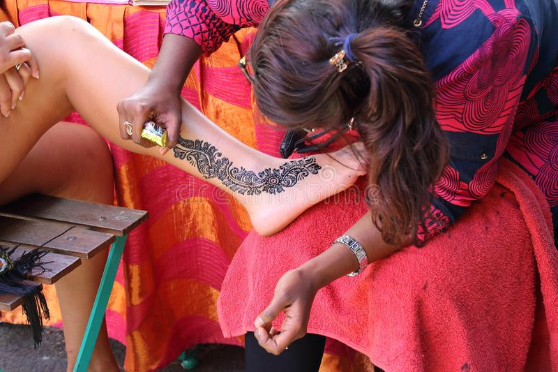 De schilderende kunstenaar van het hennalichaam op het werk royalty-vrije stock fotografie