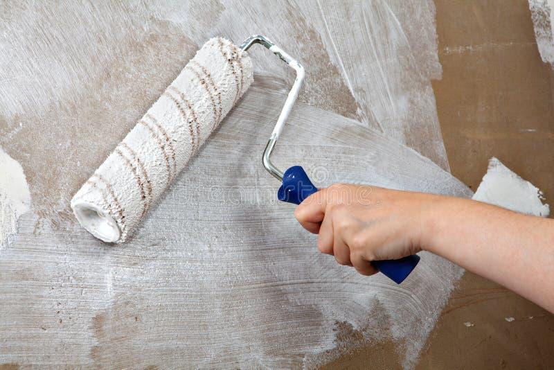 De schildershand houdt verfrol, schilderend muur met witte kleur royalty-vrije stock afbeeldingen
