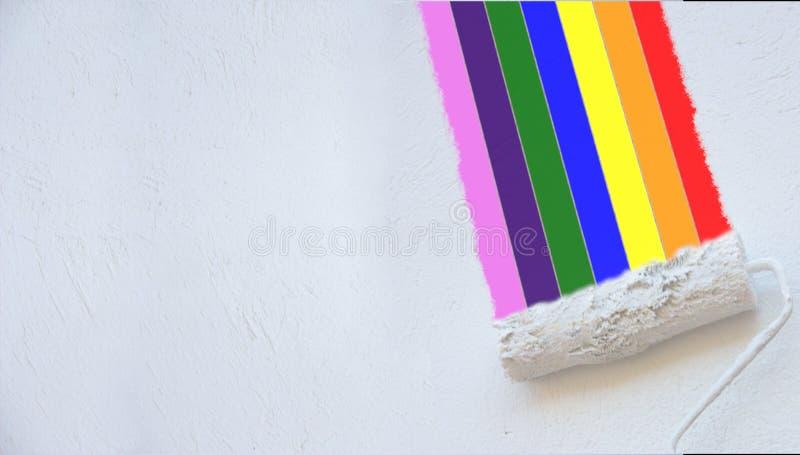 De schildersrol schildert een regenboog op een witte muur stock afbeelding