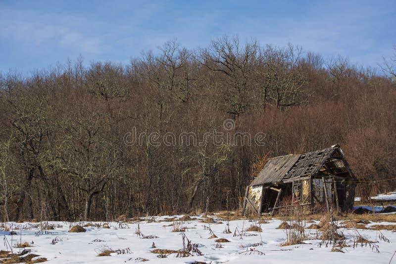 De schildertribunes van het landschaps oude dilapidated houten plattelandshuisje alleen in opheldering met sneeuw in bergen royalty-vrije stock afbeeldingen