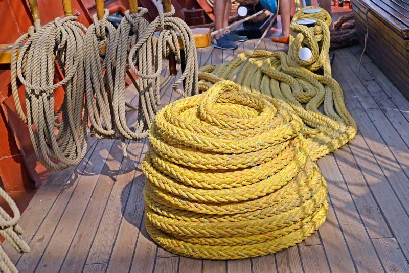 De schipkabel omgezet in de baai ligt op het dek van het varende schip stock foto's