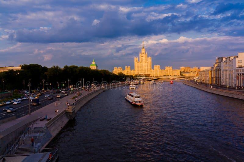 de schipzeilen op de rivier in het zonsonderganglicht cityscape en een woningbouw met een spits op de achtergrond royalty-vrije stock foto's