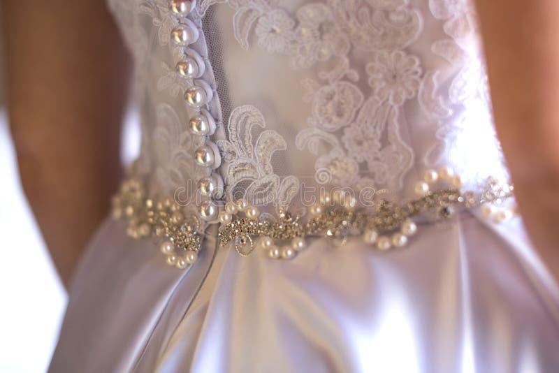 De schitterende, blondebruid in witte luxekleding wordt klaar voor huwelijk Ochtendvoorbereidingen Vrouw die op kleding zetten stock foto's