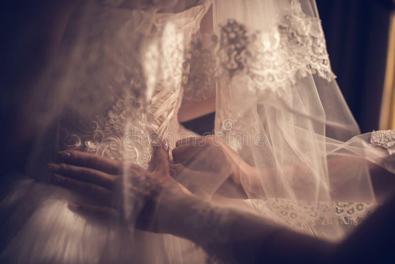 De schitterende, blondebruid in witte luxekleding wordt klaar voor huwelijk Ochtendvoorbereidingen Vrouw die op kleding zetten royalty-vrije stock fotografie