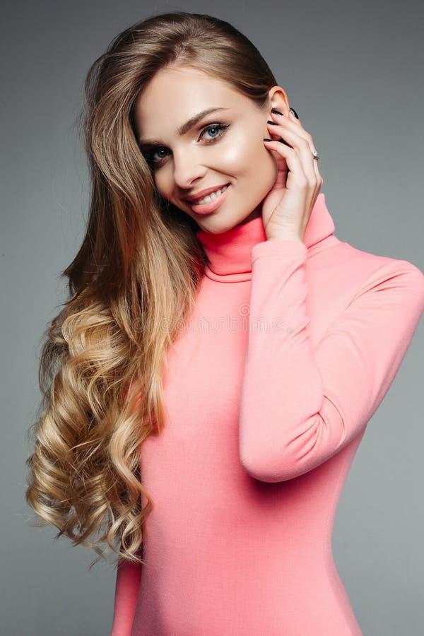 De schitterende blondevrouw in roze sweater met golvend volumed haar royalty-vrije stock afbeeldingen