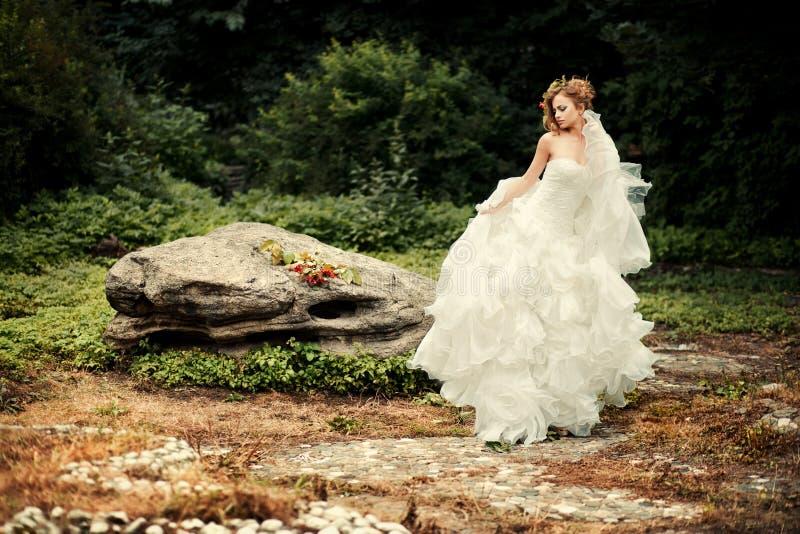 De schitterende bruid in een weelderige witte kleding danst royalty-vrije stock fotografie