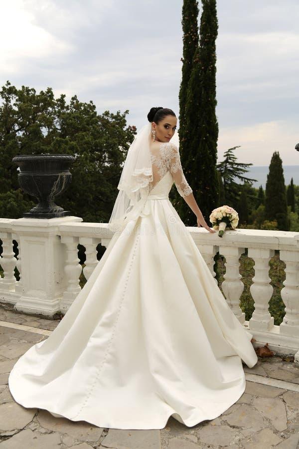 De schitterende bruid met donker haar draagt elegante huwelijkskleding royalty-vrije stock foto