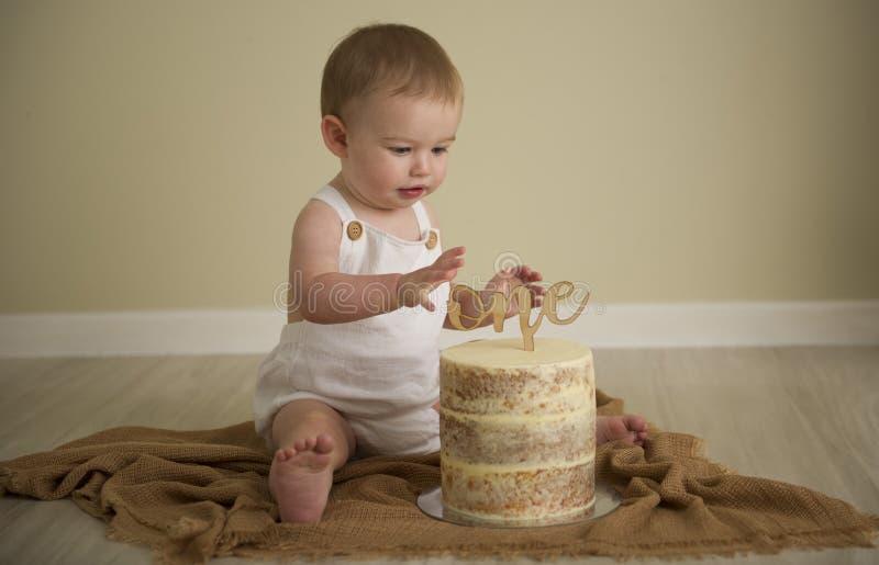 De schitterende gelukkige blauwe eyed babyjongen in neutrale tonen draait  royalty-vrije stock afbeeldingen