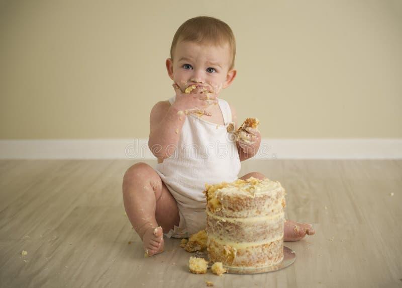 De schitterende gelukkige blauwe eyed babyjongen in neutrale tonen draait  royalty-vrije stock fotografie