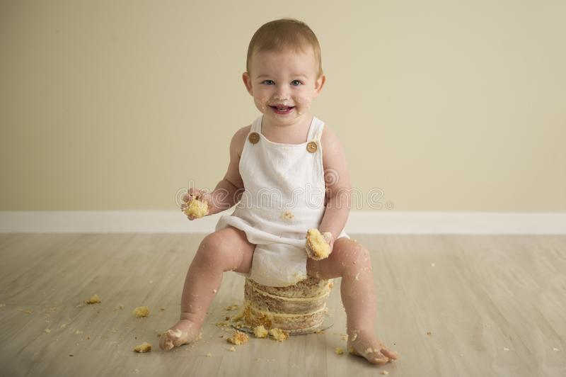 De schitterende gelukkige blauwe eyed babyjongen in neutrale tonen draait  stock afbeelding