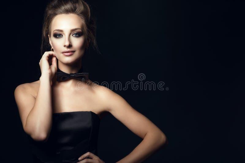 De schitterende glamvrouw met mooi maakt omhoog en updohaar die zwarte korsetkleding en vlinderdas op haar hals dragen royalty-vrije stock foto