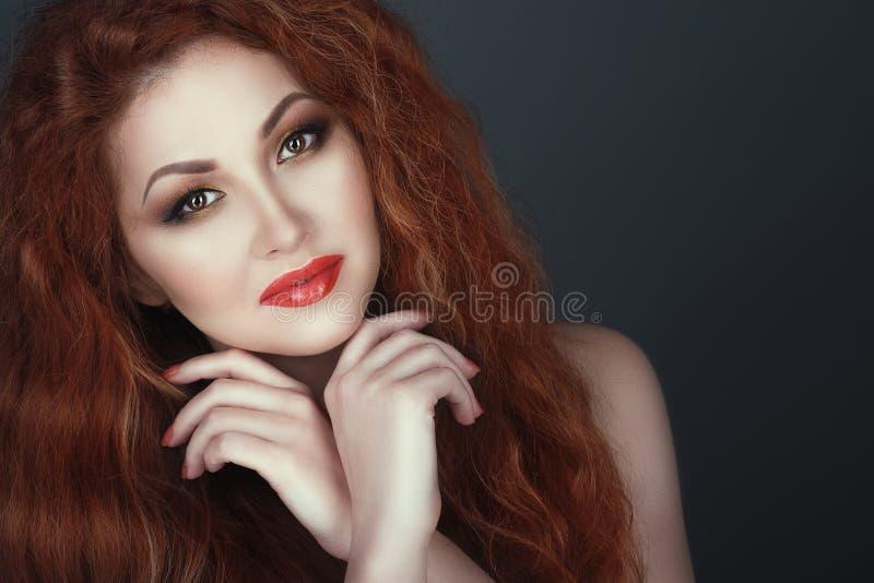De schitterende glimlachende rode geleide vrouw met mooi maakt omhoog, haar die handen onder haar kin worden gekruist royalty-vrije stock afbeeldingen