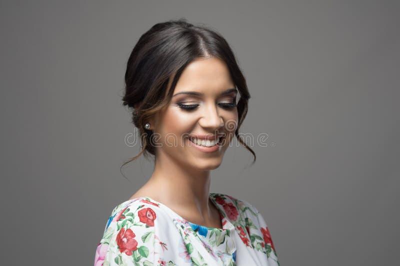 De schitterende jonge schuwe vrouw met smokeyogen maakt omhooggaande en perfecte tanden neer glimlachend en kijkend stock foto's