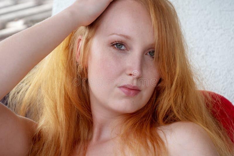 De schitterende jonge sexy naakte redheaded vrouwengember met vrije schouders kijkt sensually aan de kijker royalty-vrije stock foto