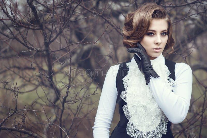 De schitterende jonge vrouw met elegant Victoriaans kapsel die haar houden dient leerhandschoen bij haar wang in stock foto's