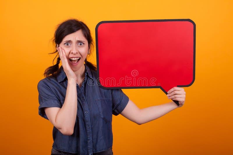 De schitterende jonge vrouw schokte status met toespraakbel in studio over gele achtergrond stock foto's