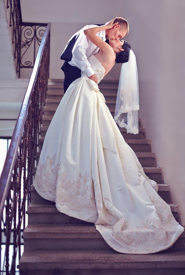 De schitterende kussen van het huwelijkspaar op treden stock foto