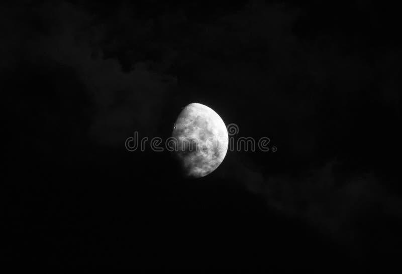 De schitterende maan in een donkerblauwe nachthemel wordt behandeld door zachte wispy donkere wolken royalty-vrije stock foto