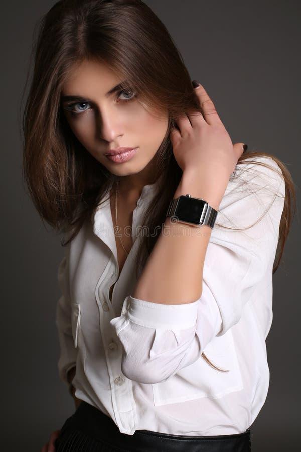 De schitterende sensuele vrouw met donker recht haar draagt elegante kleren stock foto