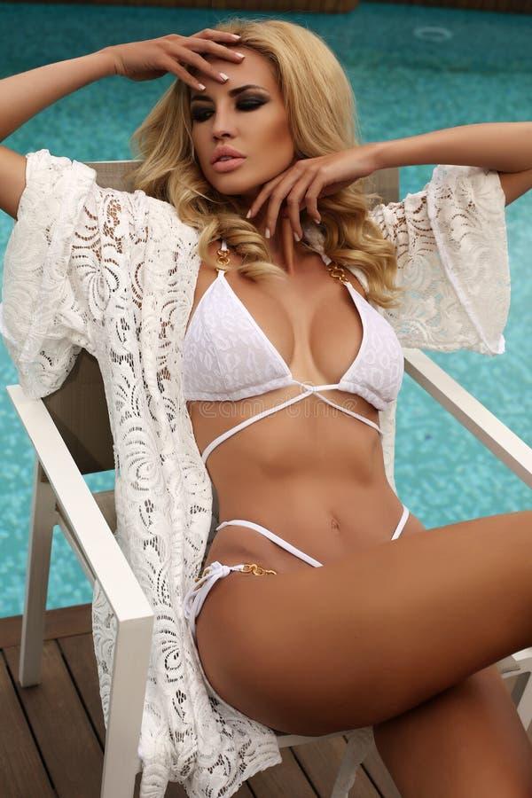 De schitterende sexy vrouw met blond haar draagt elegant zwempak royalty-vrije stock fotografie