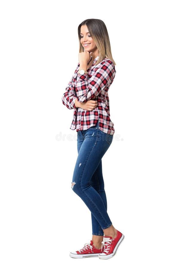 De schitterende vrouw die van de straatstijl jeans, plaidoverhemd en tennisschoenen glimlachen dragen die neer eruit zien stock foto