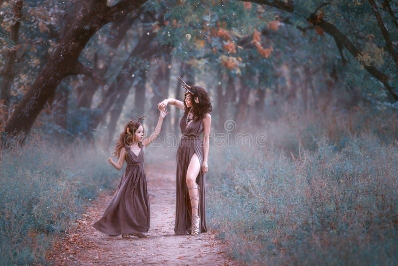 De schitterende vrouw in hertenkostuum spint haar dochter op een bossleep, die lange bruine kleding dragen, die haar tonen royalty-vrije stock afbeelding