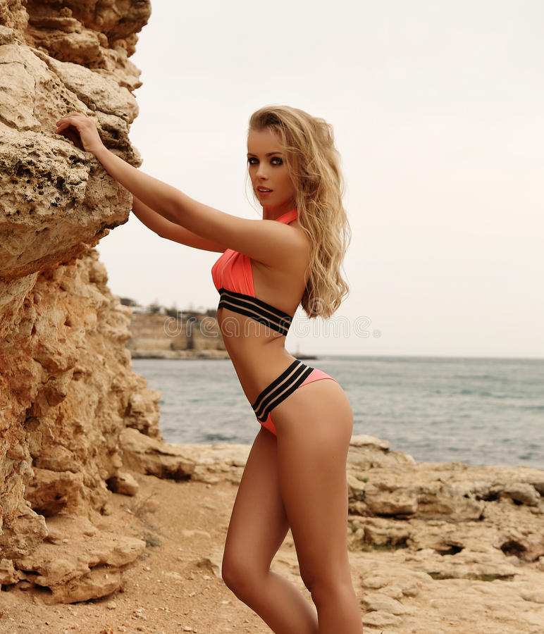 De schitterende vrouw met blond haar in het elegante zwempak stellen op is royalty-vrije stock foto's