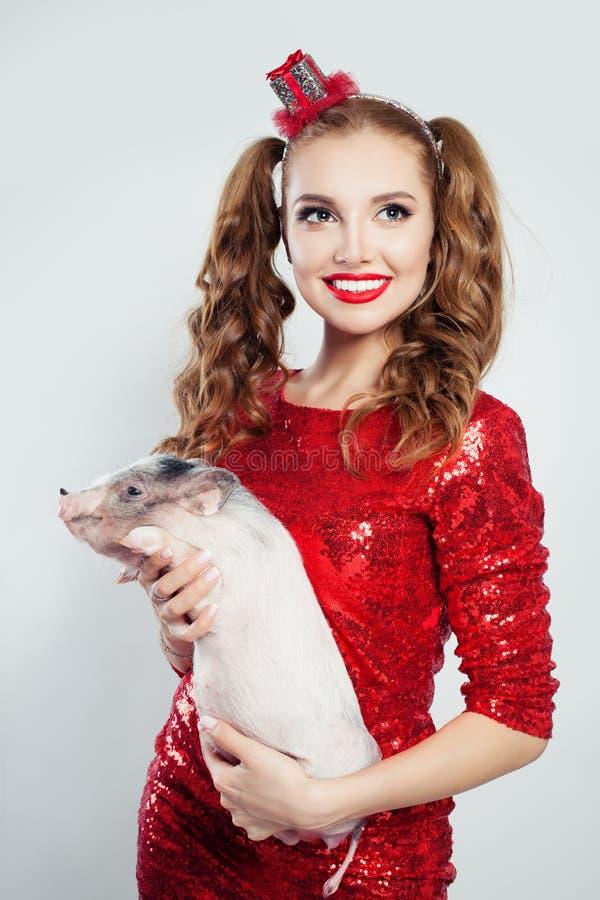 De schitterende vrouw met rode lippenmake-up en het lange haar die rode partij dragen kleden het houden van weinig varken stock afbeeldingen