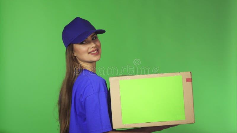 De schitterende vrouwelijke agent die van de leveringsdienst thumns tegenhoudend kartondoos tonen royalty-vrije stock foto