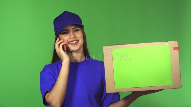 De schitterende vrouwelijke arbeider die van de leveringsdienst pakket leveren die op de telefoon spreken royalty-vrije stock fotografie