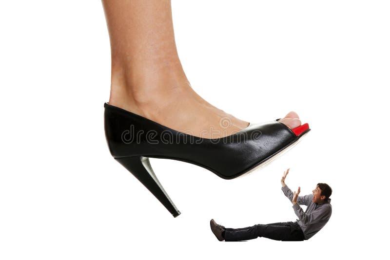 De schoen die van de vrouw op bedrijfsmannen stapt. stock foto's