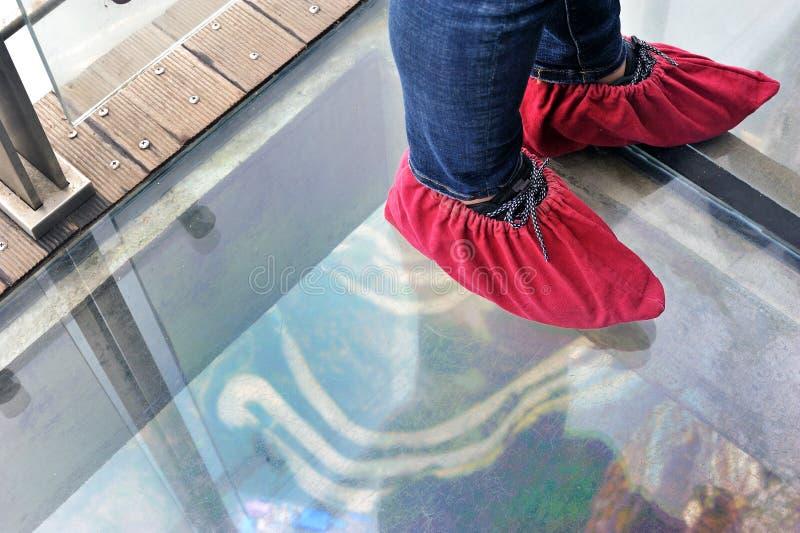 De schoen van de toerist met schoendekking en weg in Tianmenshan-aardpark, China onder glasweg royalty-vrije stock afbeelding