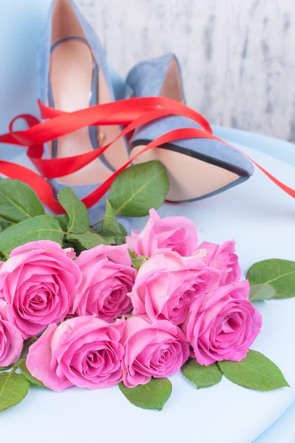 De schoenen blauwe high-heeled van vrouwen Elegante schoenen en een boeket van rozen in het binnenland Een gift voor een meisje i royalty-vrije stock fotografie