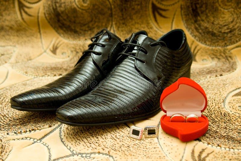 De Schoenen en de trouwringen van de bruidegom stock afbeelding