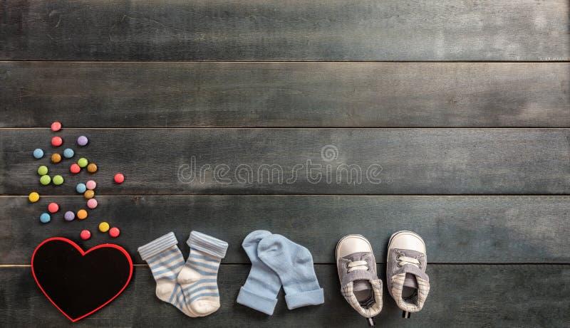 De schoenen en de sokken van de babyjongen op blauwe houten achtergrond stock foto