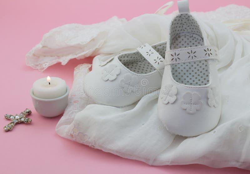 De schoenen, het kruis en de kaars van het babymeisje op wit kant met roze backgr stock foto