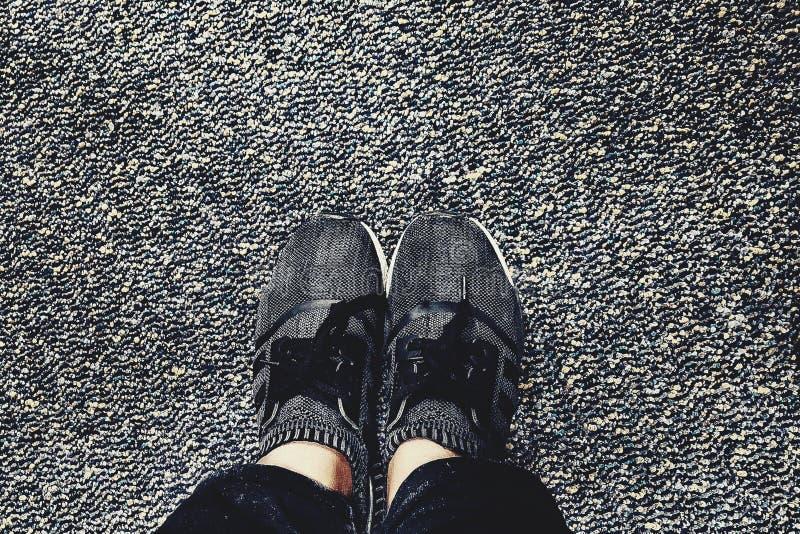 De schoenen met zwarte en grijze deurmat kijkt goed stock fotografie