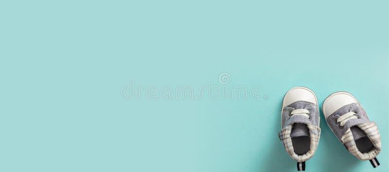 De schoenen van de babyjongen op pastelkleur blauwe achtergrond, banner stock afbeelding