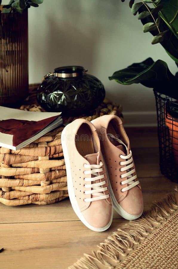 De schoenen van de beige vrouwen van het schoenen elegante leer op lichte glanzende schoenen houten als achtergrond met hielen royalty-vrije stock foto