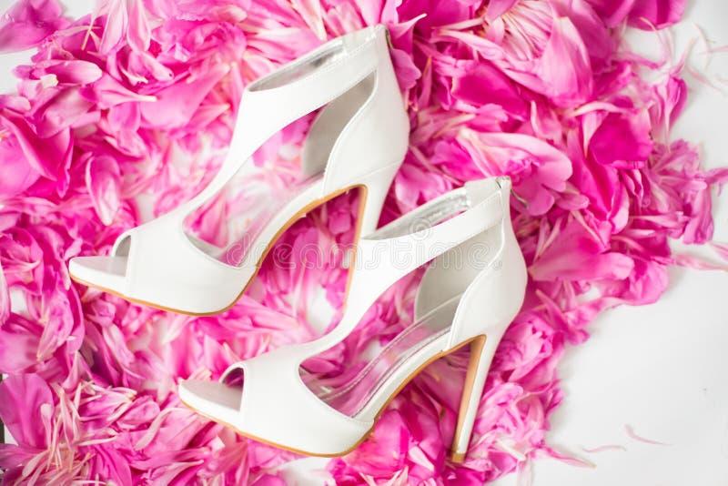 De schoenen van de bruid `s Witte bruid` s schoenen op de bloemblaadjes van pioenen Het concept van de huwelijksfoto royalty-vrije stock afbeeldingen