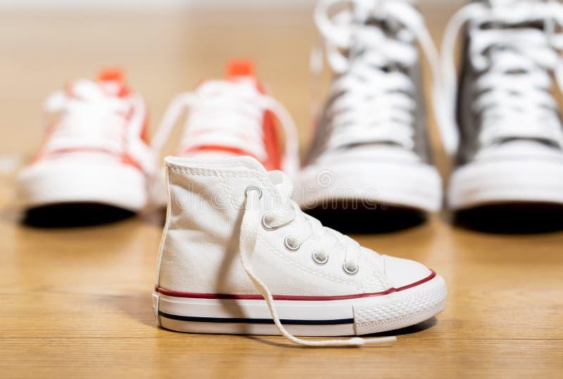 De schoenen van het tennisschoenencanvas van ouders en kind op houten vloer thuis in het verwachten van een baby gelukkige famili stock foto