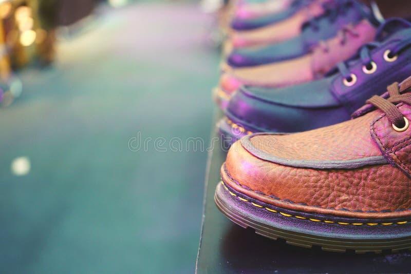 De Schoenen van leermensen op plank in de opslag stock afbeeldingen
