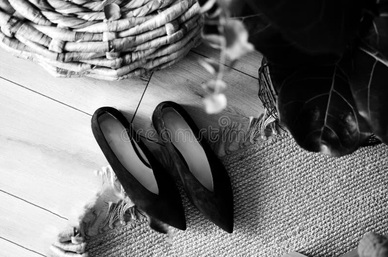 De schoenen van de zwarte high-heeled vrouwen van het schoenen elegante leer op de rotanstoel, meetkunde, steken glanzende hielsc stock foto's