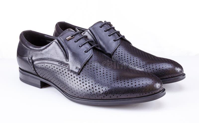 De schoenen van zwarte leermensen op witte achtergrond stock afbeeldingen