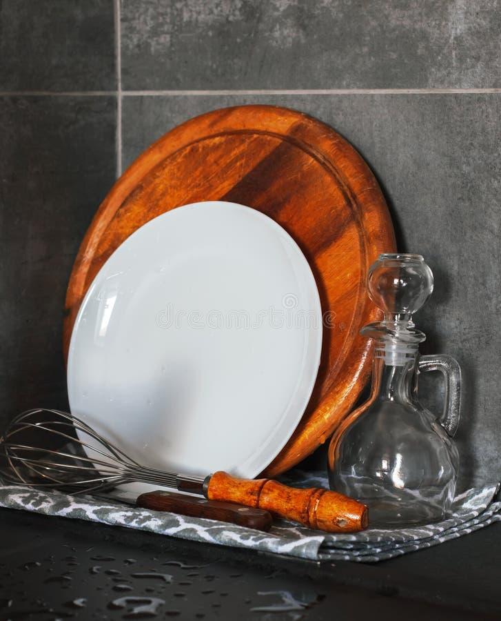 De schone gewassen schotels in een moderne keuken droogt op een handdoek Platen die Raad snijden - Beeld stock foto